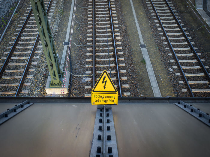 High angle view of high voltage danger sign on railroad tracks