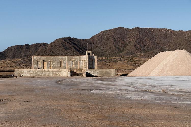 Built structure on desert against mountain range