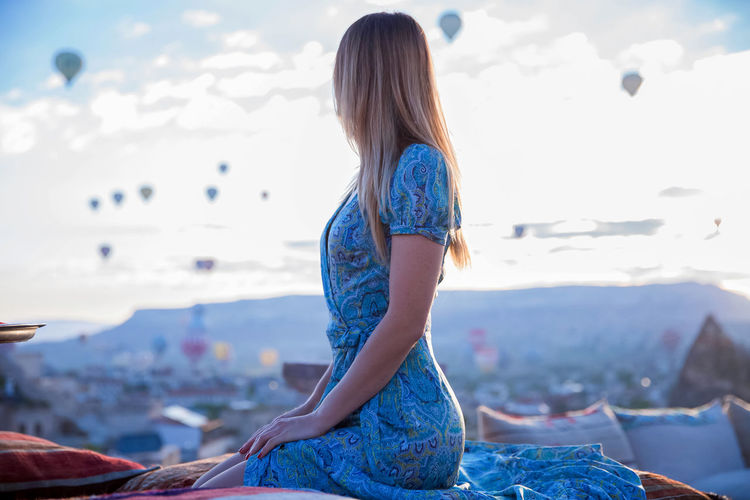 Woman sitting against sky during sunset