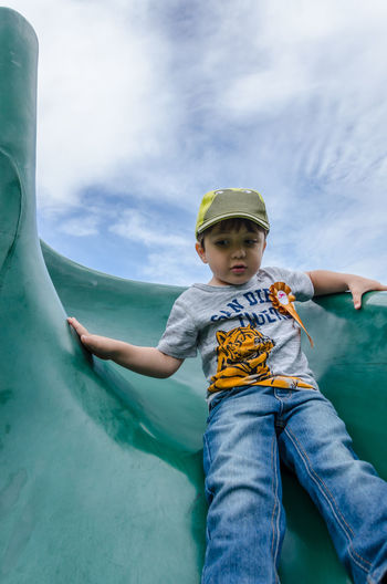 Low angle view of boy on slide against sky