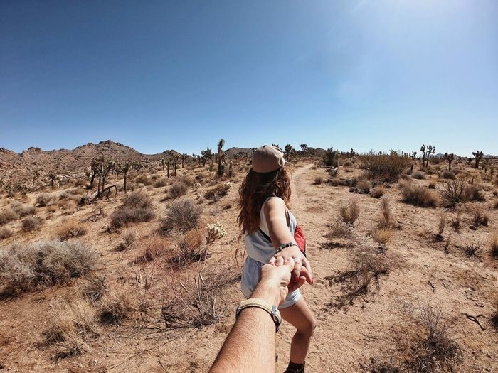 Cropped image of man holding woman hand at desert