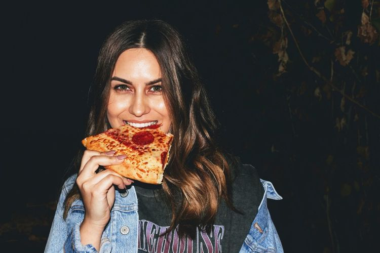 pizza in the dark EyeEm Selects Portrait Portrait Of A Woman EyeEm Best Shots Enjoying Life Young Adult Food Front View Headshot Biting Food And Drink Young Women Women Holding Females Human Body Part Black Background Eating