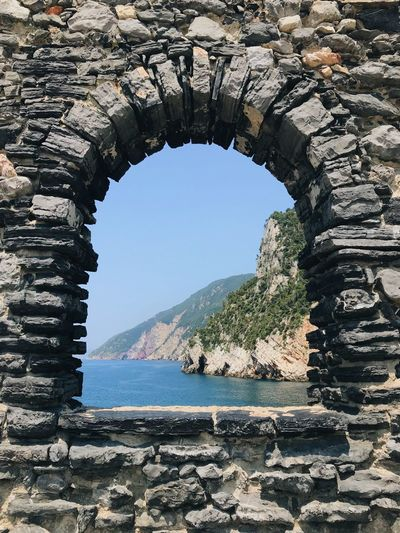Arch Architecture Beauty In Nature Built Structure Day History Mountain Natural Arch Nature No People Outdoors Rock Rock - Object Scenics - Nature Sea Sky Solid Stone Wall The Past Tranquil Scene Water