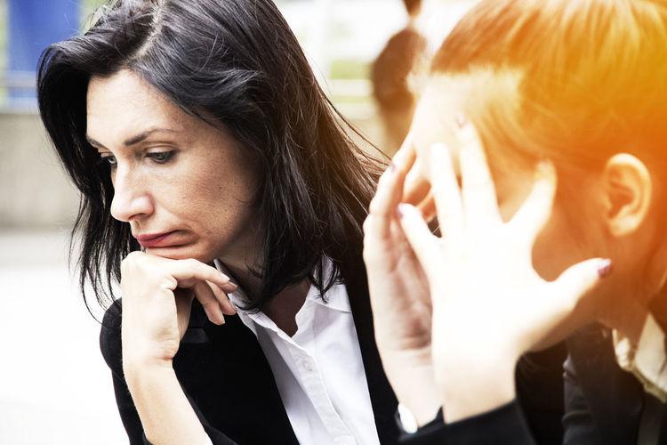 Stressed businesswomen sitting outdoors