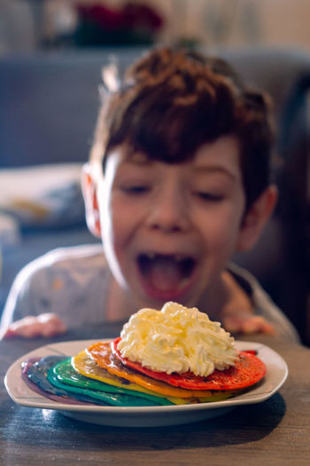 Portrait of boy with pancakes and cream in plate