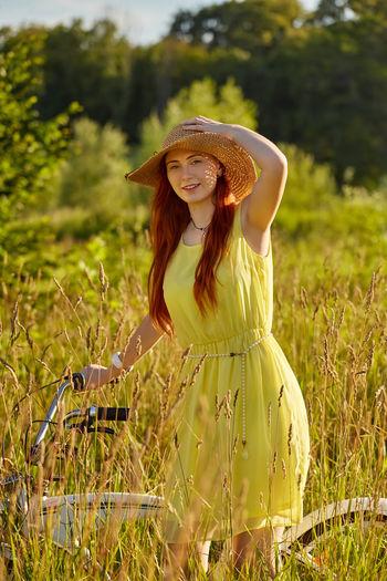 Portrait of woman standing by plants on field