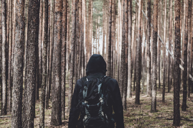 Man in hooded shirt standing against trees
