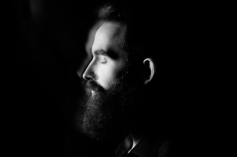Close-up portrait of man looking away against black background
