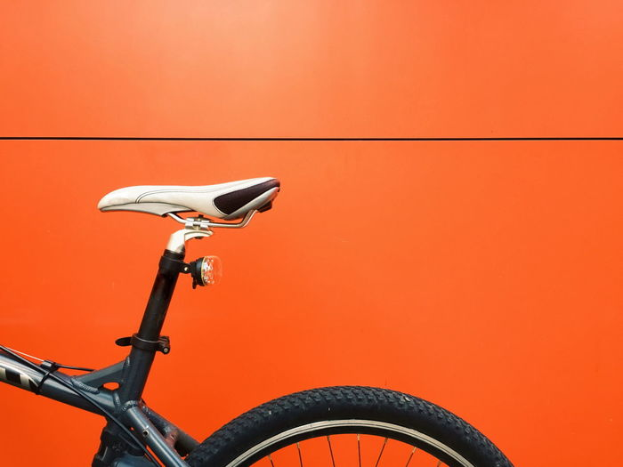 Bicycle parked against orange wall