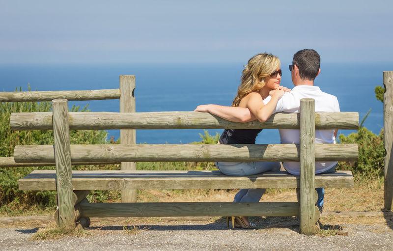 People sitting on railing against sky