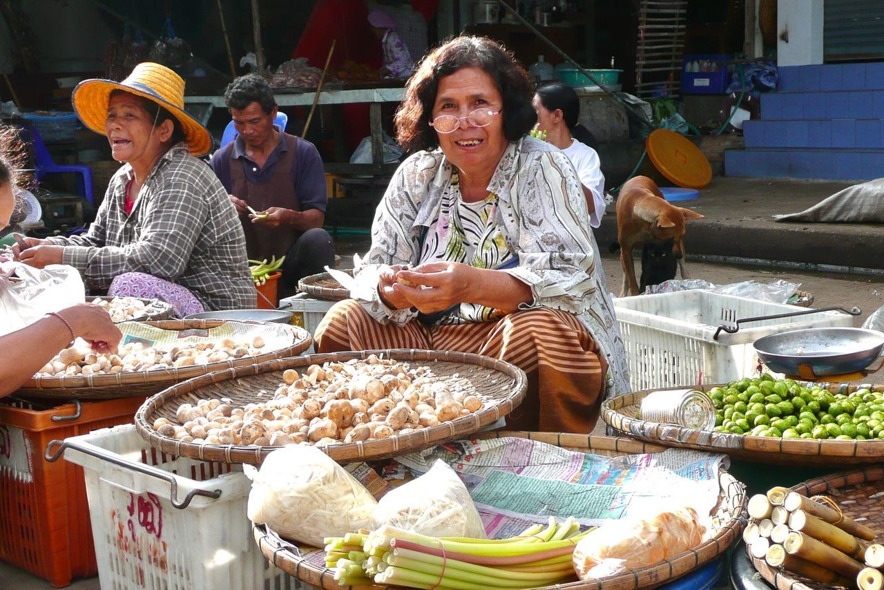 real people, food and drink, market vendor, incidental people, looking at camera, portrait, lifestyles, food, outdoors, market, day, retail, freshness, smiling, sitting, men, young adult, people