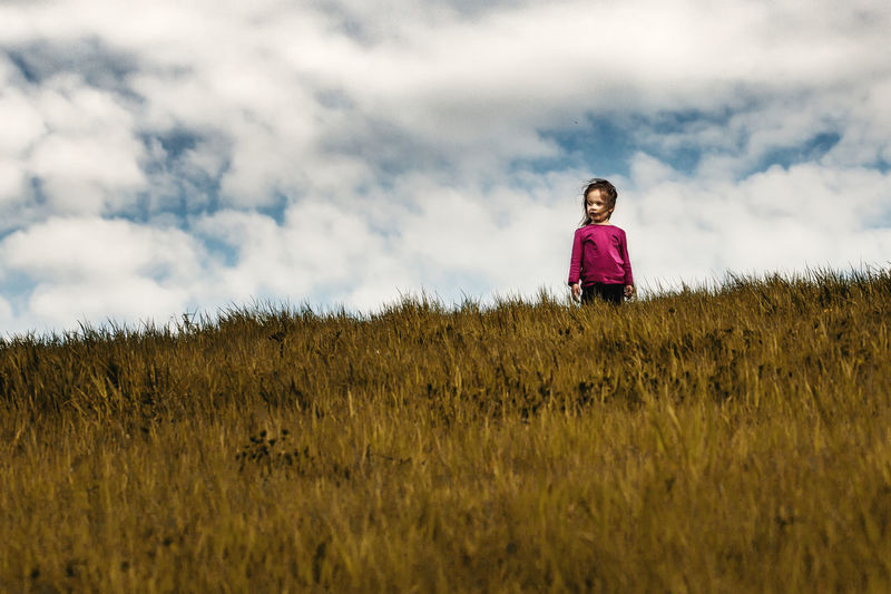 Girl Standing On Field Against Sky