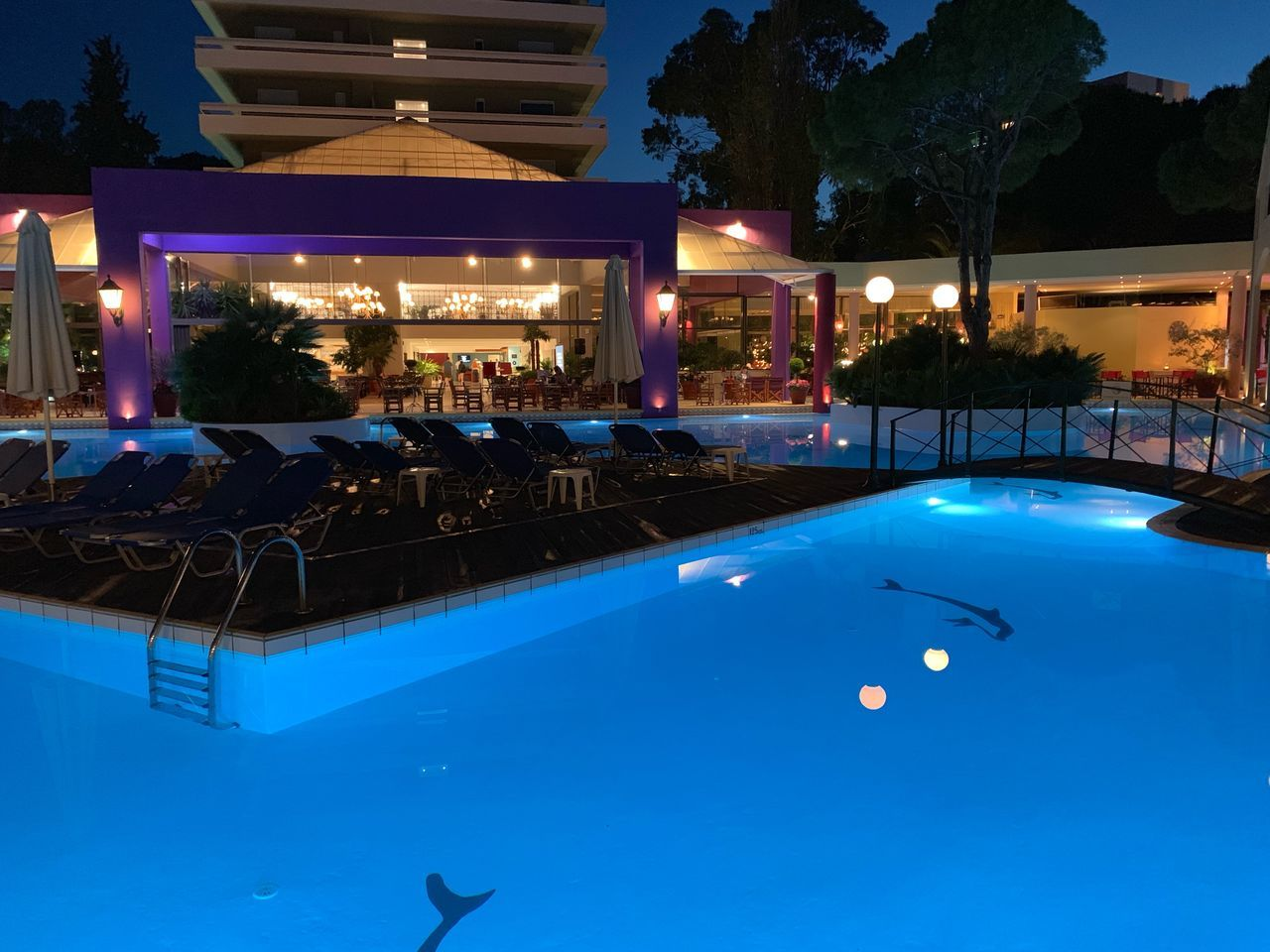 pool, swimming pool, illuminated, night, built structure, architecture, nature, lighting equipment, building exterior, water, blue, dusk, tree, no people, chair, tourist resort, outdoors, table, seat, luxury, turquoise colored