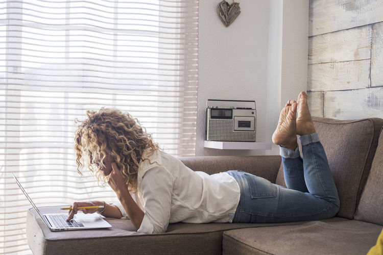 Curly woman at home lay down and use computer laptop on the sofa in reverse position - indoor working in alternative office - housewife managing and doing business - free people lifestyle - modern internet technology Furniture Sofa Wireless Technology Technology One Person Indoors  Sitting Home Interior Relaxation Communication Lifestyles Domestic Room Adult Casual Clothing Young Adult Living Room Lying Down Leisure Activity Hair Hairstyle Using Laptop Feet Up Caucasian People Curly Hair Relaxing Laptop Blogger Alternative Office Business Chatting Housewife Freedom Adult Connection Jeans Freelance Work