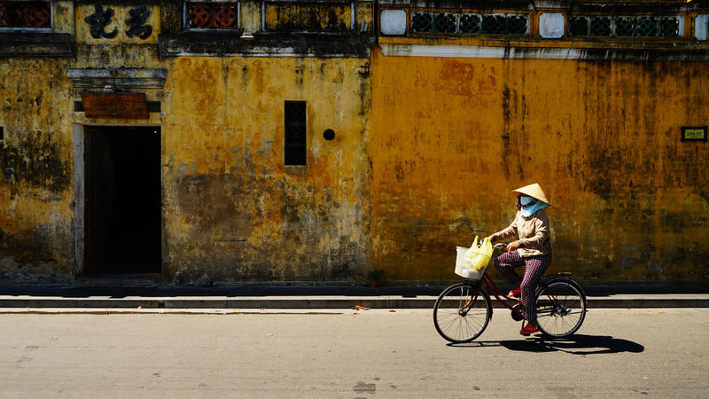 A woman is cycling along the pavement at Hoi an, Vietnam. Ancient Ancient Civilization Architecture Bicycle Building Exterior Built Structure City Day Full Length Hoian  Hoian, Vietnam Lifestyles Men One Person Outdoors People Real People Riding Shadow Town TOWNSCAPE Transportation Vintage Vintage Cars Young Adult