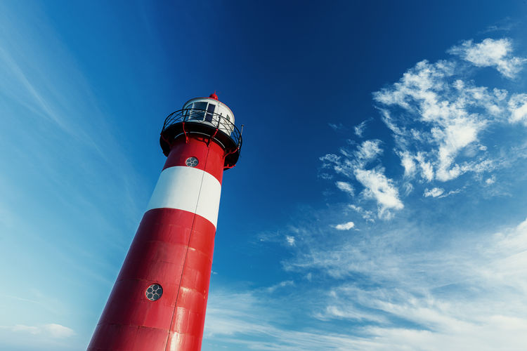 Lighthouse against blue sky Architecture Blue Building Exterior Built Structure Cloud - Sky Danger Day Direction Lighthouse Low Angle View Netherlands No People Ocean Outdoors Protection Red Safety Security Security System Sky Westkapelle
