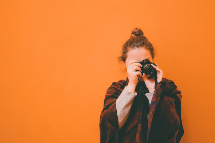 Front View Of Woman Photographing Against Orange Background