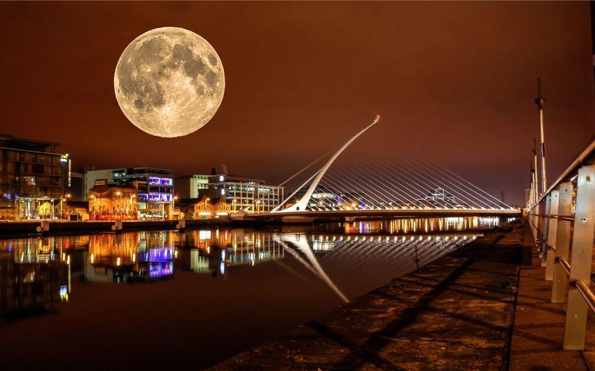Full Moon Over Illuminated City