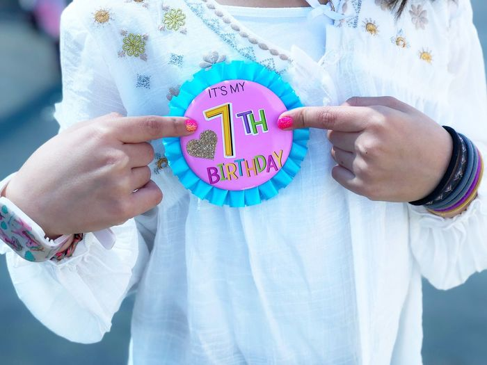 A child's 7th birthday celebration Holding One Person Text Real People Western Script Midsection Communication Front View Casual Clothing Human Hand Standing Hand Child Day Heart Shape Message