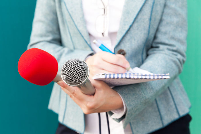 Female journalist taking notes, holding two microphones at a press conference. Public relations-PR Notebook Censorship Journalist Mic PR Press Reporting Writing Broadcast Broadcasting Female Hands Information Interviewing Journalism Media Microphone News News Event Notes Pencil Press Conference Question Recording Reporter Unrecognizable Person