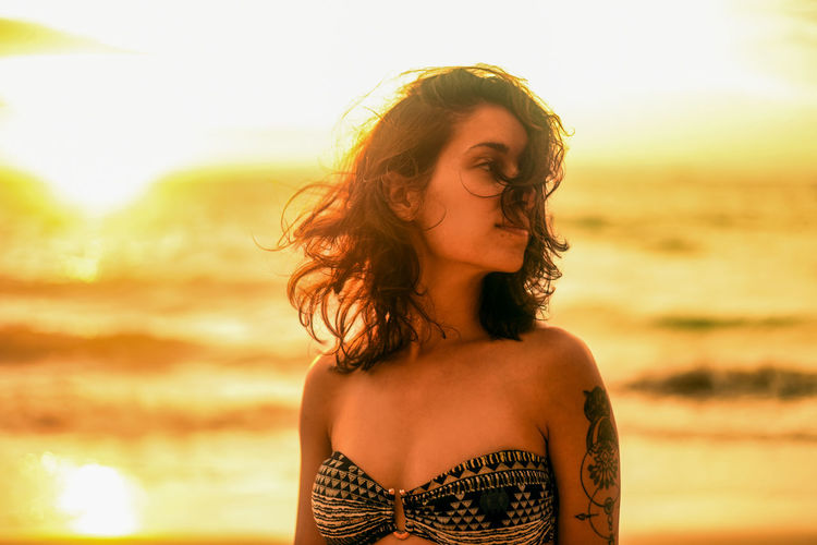 Thoughtful young woman with tousled hair standing at beach during sunset