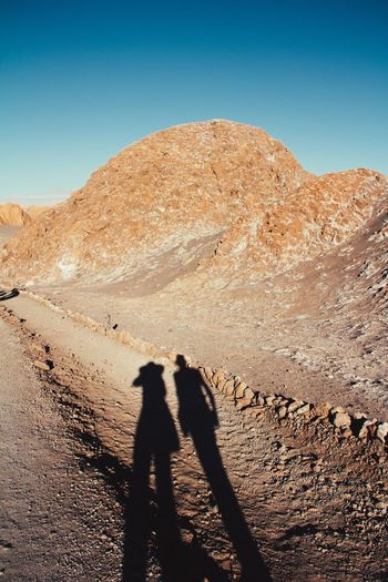 Shadow of two people on desert against clear sky