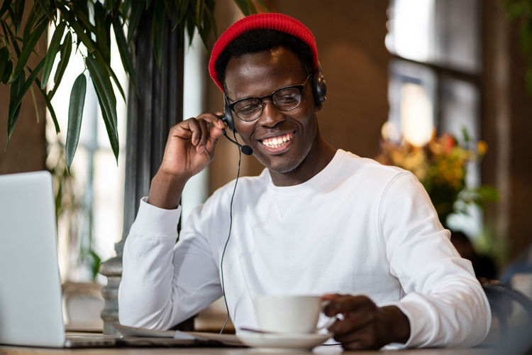 Smiling man wearing headphones sitting at cafe