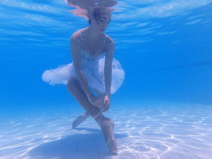 Ballerina wearing ballet shoe in swimming pool