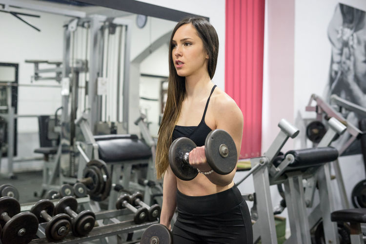 Adult Bicep Body Conscious Dumbbell Effort Equipment Exercising Gym Health Club Healthy Lifestyle Indoors  Lifestyles Muscular Build One Person Sport Sports Training Strength Vitality Weight Weight Training  Weights Wellbeing Young Adult Young Women