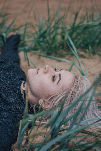 Portrait of woman lying down on field