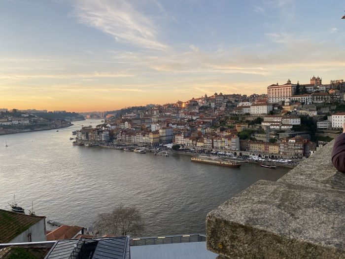 High angle view of river by buildings against sky during sunset