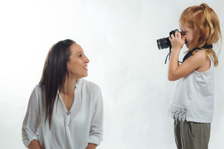 The Photographer Adult Camera - Photographic Equipment Child Digital Camera Indoors  Little Girl People Photographer Photographing Photography Themes Smiling Standing Studio Shot Technology Two People White Background
