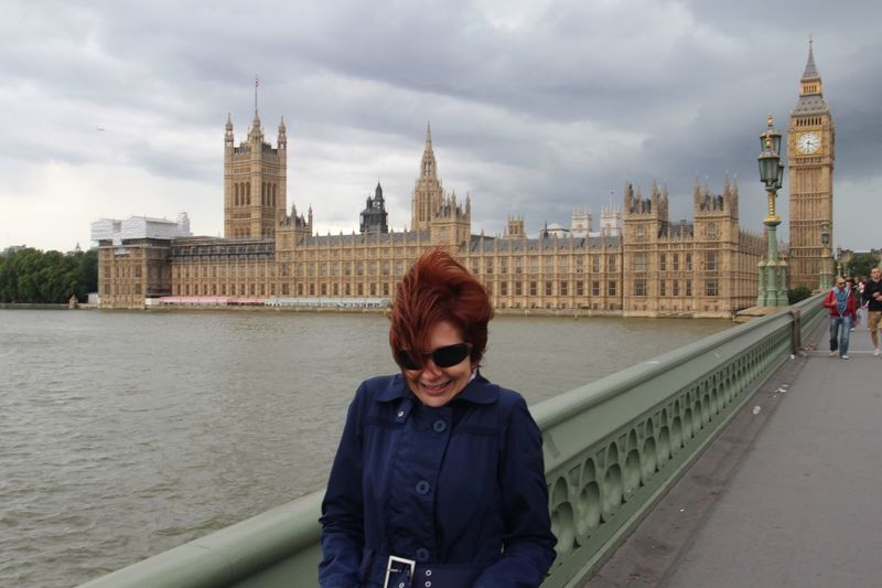 Woman in sunglass on westminster bridge over thames river in city