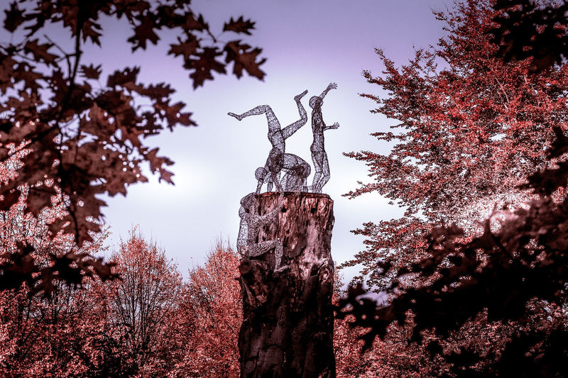 Low angle view of angel statue against trees