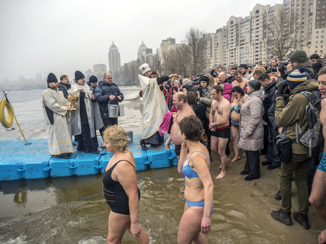 Great Christian holiday Epiphany on the banks of the Dnieper Architecture Banks Building Exterior Built Structure Casual Clothing Christian City Clear Sky Cold Dnieper Epiphany Full Length Great Holiday In Front Of Large Group Of People Lifestyles People And Places Person Priest Religion River Standing Togetherness Winter
