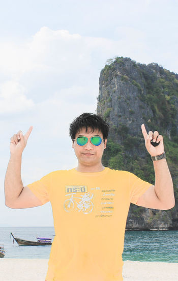 Sea Casual Clothing Day Front View Gesturing Human Arm Leisure Activity Lifestyles Men Nature One Person Outdoors Portrait Real People Sea Sky Standing Sunglasses Waist Up Water