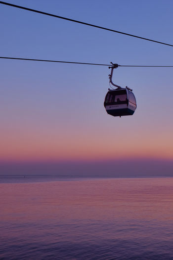 Overhead cable cars over sea against sky during sunset