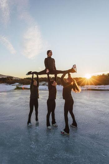 Full length of friends standing on shore against sky during sunset