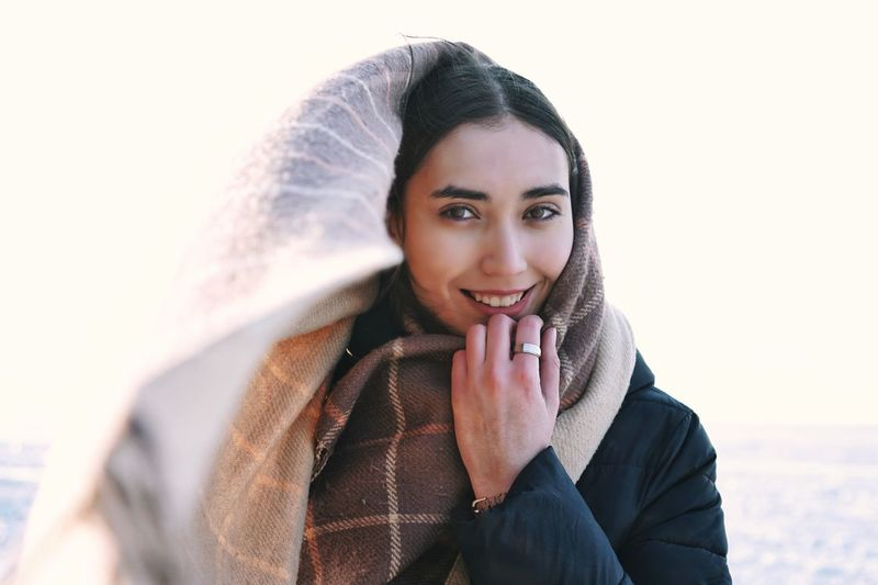 Portrait of smiling woman wearing scarf during winter