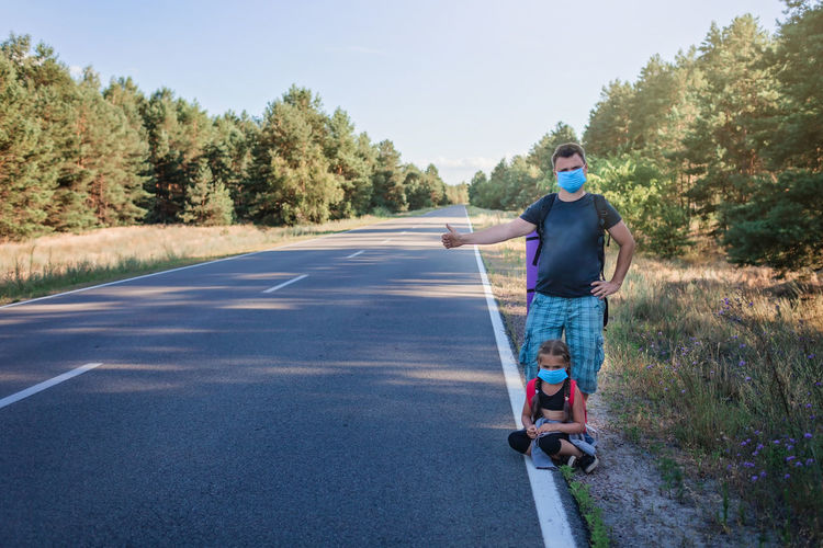 Man standing on road against trees