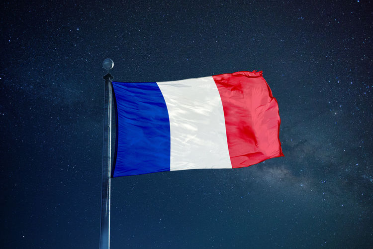 Low angle view of french flag against star field sky