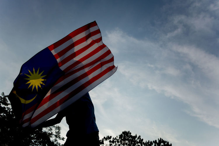 A man waving Malaysian flag. Independence Day concept. ASIA Country Independence Man Patriotic Proud Silhouette Waving Boy Cloud - Sky Day Flag Holding Independence Day Low Angle View Malaysia Nation Nature One Person Outdoors Patriotism Real People Sky