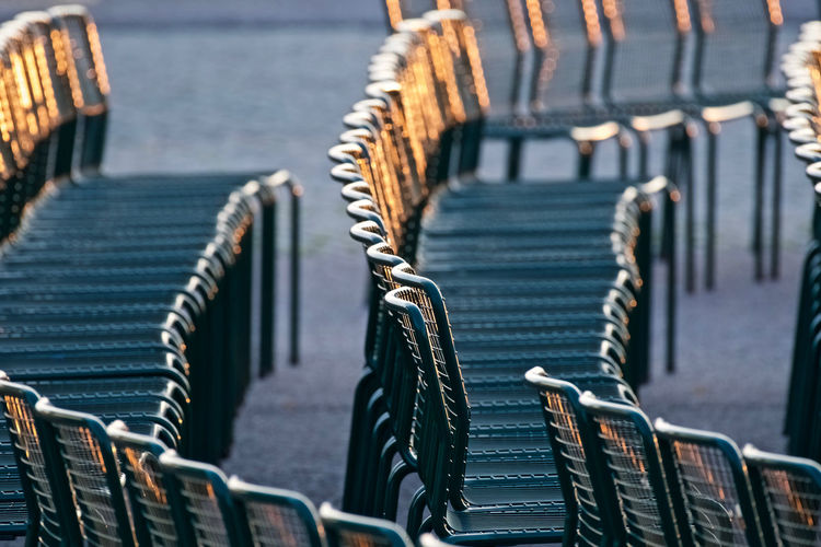 Empty chairs on footpath during sunset