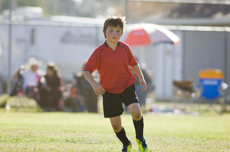 Full length of boy standing on soccer field