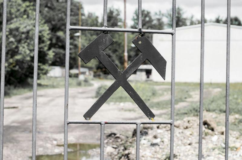 Close-up of black sign hanging on metal fence