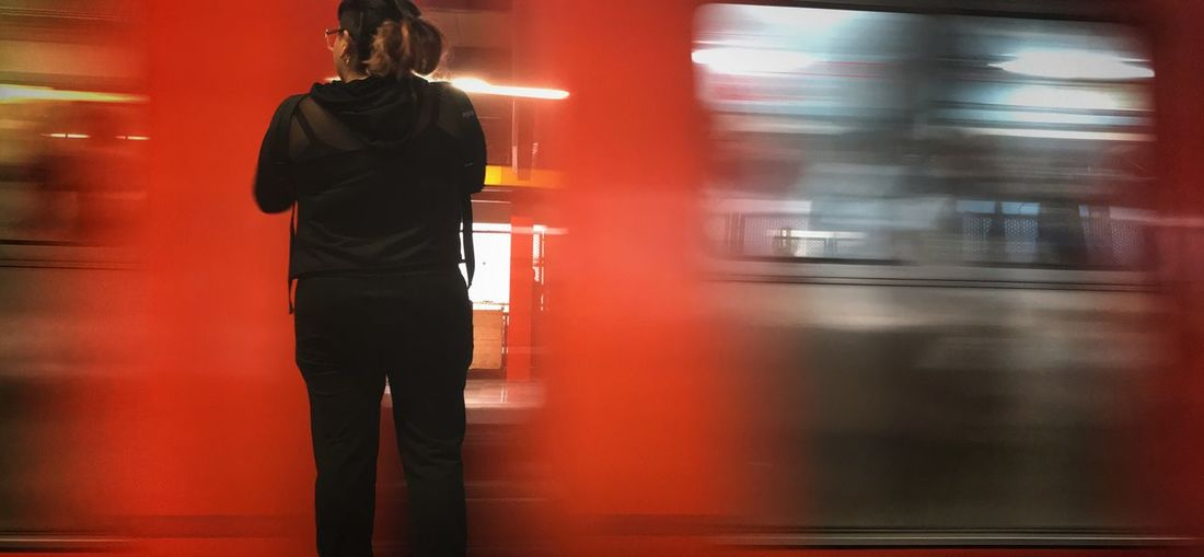Rear view of woman standing by moving train