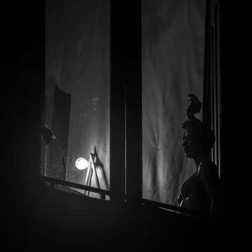 Statue of illuminated lamp in dark room