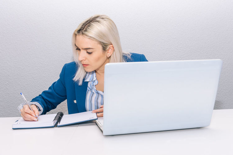 Businesswoman writing in diary on desk