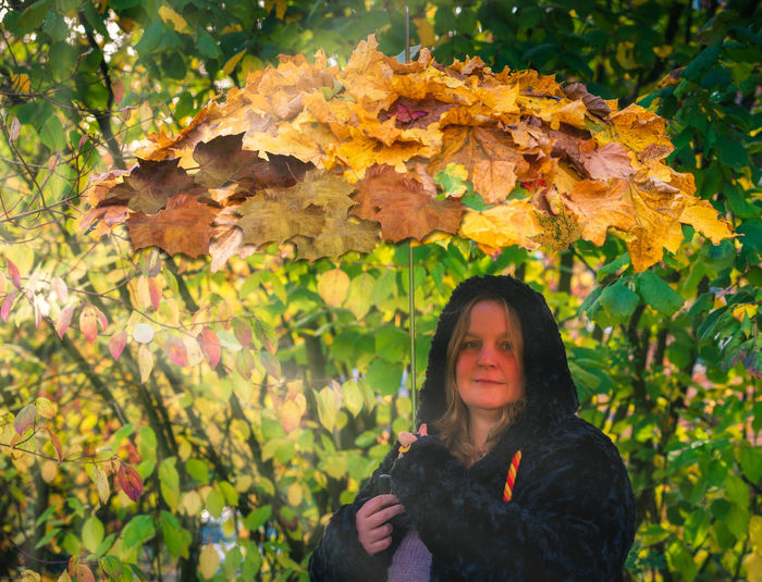Female model holds an umbrella with autumn leaves on it in hand to the autumn beginning