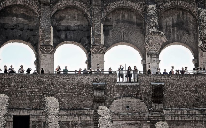 Low angle view of tourists visiting coliseum